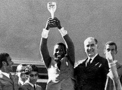 Pelé ergue o troféu de campeão do mundo ao lado de Médici.