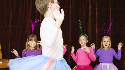 Meninos e meninas com saias de balé em um festival escolar.