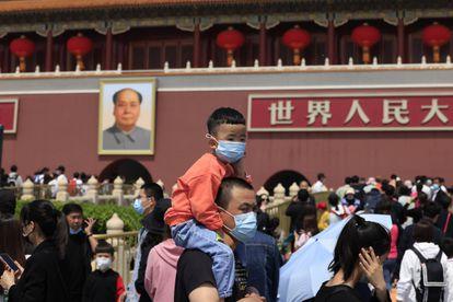 Homem carrega uma criança usando máscaras na visita à Cidade Proibida, em Pequim.