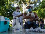"""AME772. RÍO DE JANEIRO (BRASIL), 26/05/2021.- Una trabajadora de la salud aplica hoy una dosis de la vacuna de AstraZeneca contra la covid-19 a una habitante de calle, en Río de Janeiro (Brasil). El programa """"Consultório na Rua"""" (Consultorio en la calle) ya ha vacunado en una semana a más de 200 personas que viven en las calles de Río. EFE / André Coelho"""
