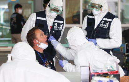 Agentes sanitários colhem amostras para exames de coronavírus no aeroporto de Incheon, na Coreia do Sul, na última sexta-feira.