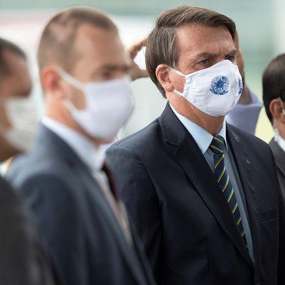 AME1058. BRASILIA (BRASIL), 20/05/2020.- El presidente de Brasil, Jair Bolsonaro (2d), sale del Palacio do Alvorada este miércoles, en Brasilia (Brasil). Brasil, el tercer país con más casos de COVID-19 en el mundo, superó este martes por primera vez la barrera de las 1.000 muertes diarias de coronavirus y registró 1.179, hasta un total de 17.971 desde el inicio de la pandemia, un récord en medio de una laguna institucional en el Ministerio de Salud. Este martes el discurso de Bolsonaro en defensa de la cloroquina, que carece todavía en el mundo científico de estudios suficientes para avalar su efectividad, sufrió otro revés por parte de la comunidad médica brasileña. EFE/ Joédson Alves