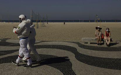 """Tercio Galdino, 66, e sua mulher Aliceia, 65, usam """"roupas espaciais"""" de proteção enquanto passeiam por Copacabana."""
