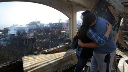 Casal se abraça na janela da casa onde morava.