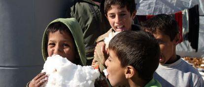 Crianças brincam com neve em um campo de refugiados no Líbano.