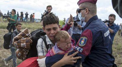 Policial húngaro barra a passagem de crianças refugiadas em Röszke (Hungria), em 8 de setembro de 2015.