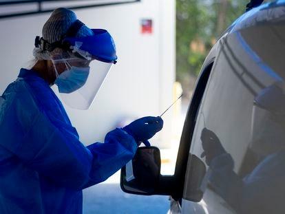 Profissionais colhem amostras de indivíduos em seus veículos para o exame PCR e análise de coronavírus no hospital militar de Sevilha (Espanha).
