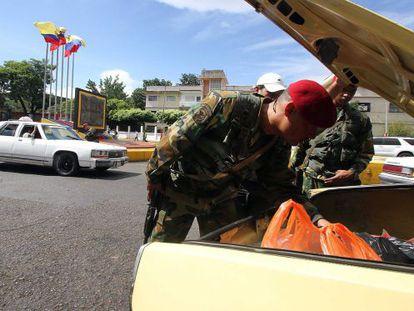 Militares venezuelanos revistam o conteúdo de um carro.