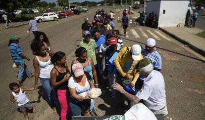 Brasileiro distribui pães a refugiados venezuelanos.