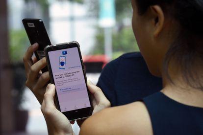 Funcionários do Governo de Singapura fazem uma demonstração do aplicativo TraceTogether.
