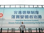 A man walks past a government advertisement to promote the new Hong Kong electoral system reform, in Hong Kong, March 30, 2021. China's top legislature approved amendments to Hong Kong's constitution on Tuesday that will give Beijing more control over the make-up of the city's legislature. (AP Photo/Kin Cheung)
