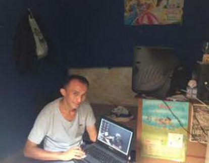 Jorge Matos, com seu notebook no colo, em sua casa, em Paraisópolis.