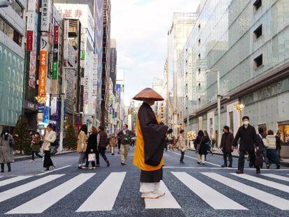 Um homem trajado de acordo com os antigos costumes cruza uma faixa de pedestres da rua Ginza, a via comercial mais cosmopolita de Tóquio