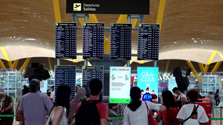 Passageiros observam informações sobre voos no terminal 4 do aeroporto Adolfo Suárez, em Madri, neste domingo.