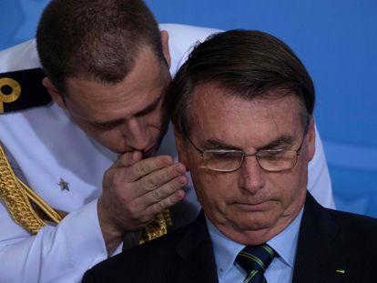 Um militar fala ao ouvido de Bolsonaro.
