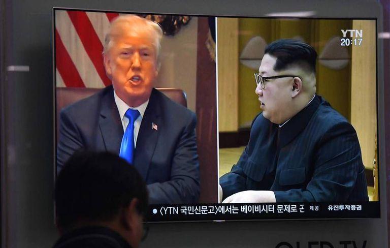 Um homem olha imagem de Trump e Kim na televisão.