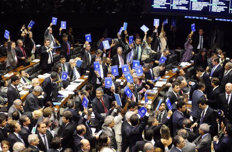 Deputados mostram carteiras de trabalho gigantes em protesto na Câmara.