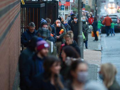 Dezenas de pessoas fazem fila do lado de fora de um supermercado em Londres, nesta terça-feira.
