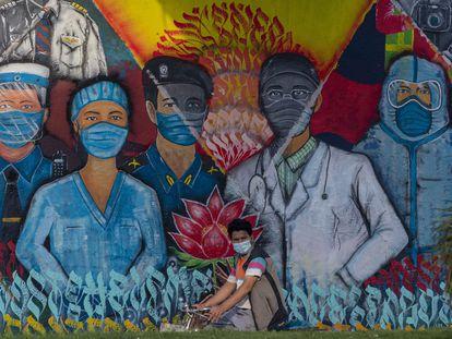 Ciclista passa em frente a mural em Katmandu, no Nepal, nesta sexta-feira.