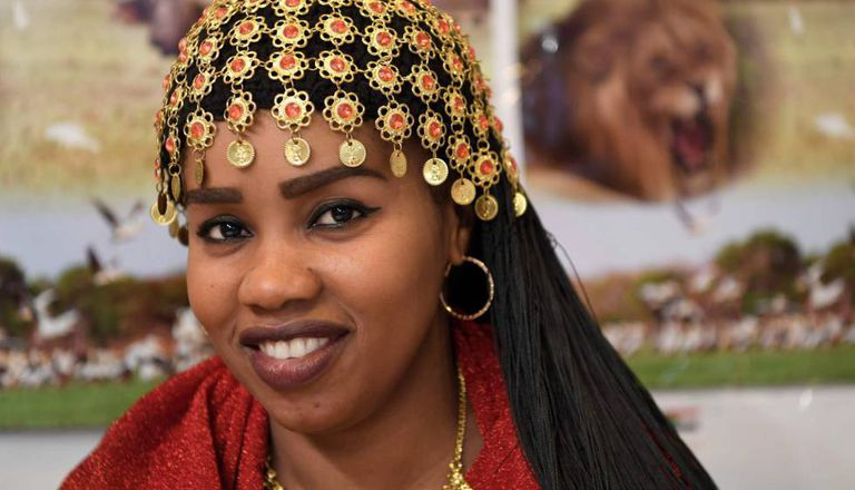 Mulher com penteado tradicional do Sudão posa no estande promocional de seu país na Feira Internacional de Turismo de Madri (Fitur).