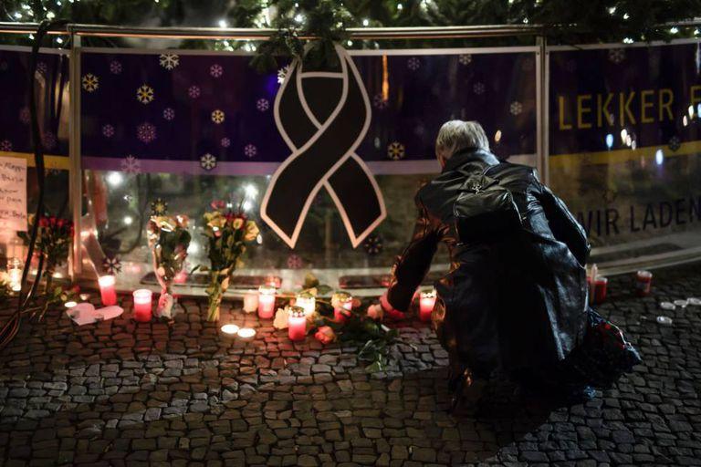 Mulher presta homenagem a vítimas do atentado, nesta terça-feira.