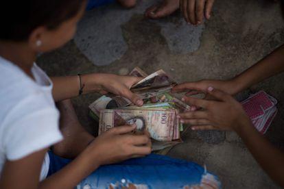 Crianças brincam com notas de bolívar não utilizadas na Venezuela em 9 de setembro.