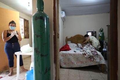 Enfermeira Angela Maria Reis se prepara para tomar conta de Erystenys Reis da Costa, 45, contagiada pela covid-19, em Manaus.