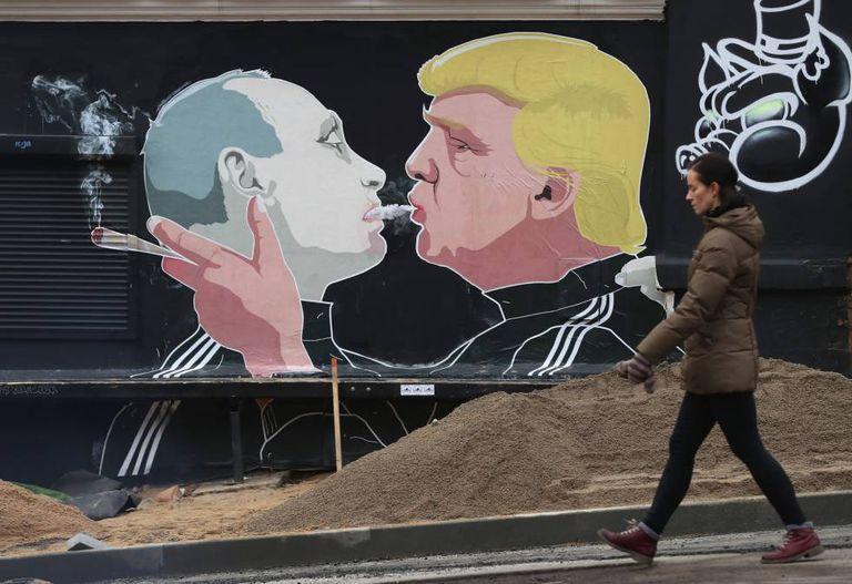 Uma mulher ao lado de um mural com a imagem de Trump e Putin em Vilnius, na Lituânia.
