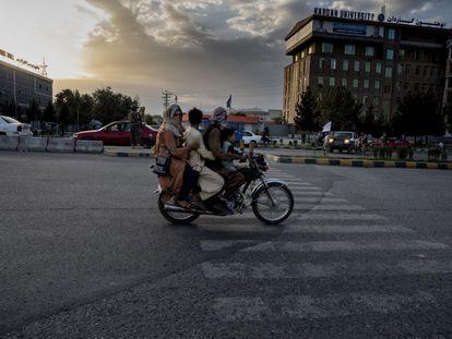 Uma família afegã passa de moto por uma rua de Cabul perto de um posto de controle dos fundamentalistas.
