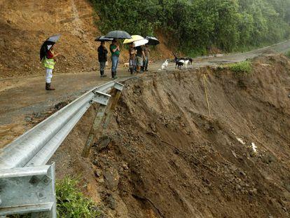 Algumas pessoas olham uma estrada parcialmente destroçada pelas chuvas em Costa Rica.