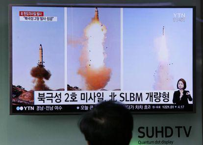 Homem vê uma televisão que transmite imagens do lançamento de um míssil na Coreia do Norte.