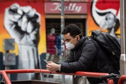 Um homem olha a tela de seu celular durante a pandemia.