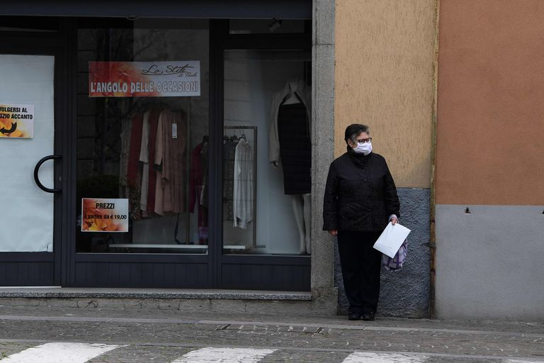A woman wearing  aface pask stands in a deserted street of Albino near Bergamo, Lombardy, on March 25, 2020, during the country's lockdown following the COVID-19 new coronavirus pandemic. (Photo by MIGUEL MEDINA / AFP)