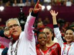 (FILES) In this file photo taken on July 31, 2012, US women gymnastics team's coach John Geddert celebrates with the rest of the team after the US  won gold in the women's team artistic gymnastics event at the London Olympic Games. - Geddert has been charged with human trafficking and criminal sexual conduct, prosecutors said on February 25, 2021. Michigan Attorney General Dana Nessel unveiled a 24-count complaint against Geddert, who owned a training facility where convicted sex offender Larry Nassar served as the gym doctor. (Photo by - / AFP)