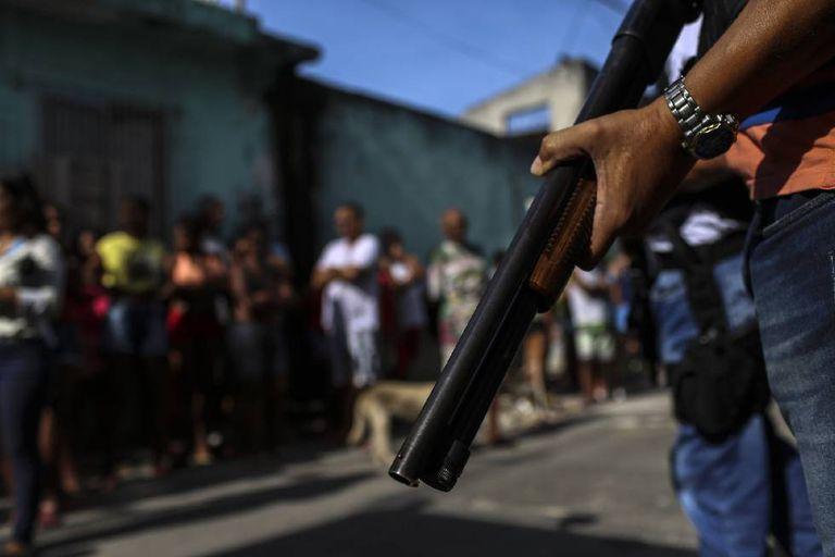Moradores de Vitória se aglomeram enquanto a polícia civil retira os cadáveres de duas mulheres assassinadas.