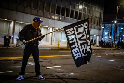 Manifestante com uma bandeira do movimento Black Lives Matter em Rochester, Estado de Nova York.