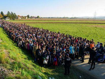 Policiais diante dos imigrantes que acabavam de cruzar a fronteira entre a Croácia e a Eslovênia, em outubro de 2015