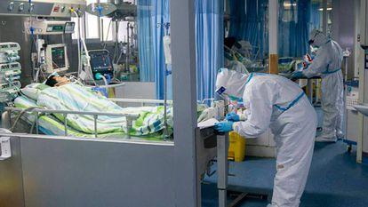 Médico com um paciente na unidade de terapia intensiva do hospital Zhongnan, em Wuhan.