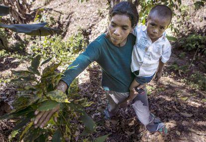 Uma mulher e seu filho com uma planta atingida.