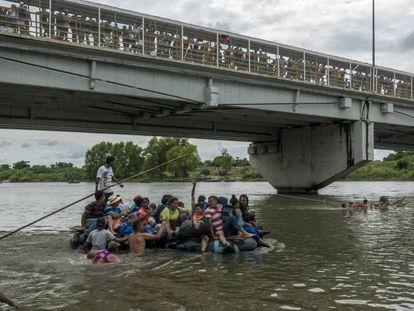 Migrantes cruzam em balsa o rio Suchiate para chegar ao México.