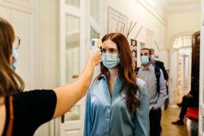 Funcionária mede a temperatura de seus colegas na entrada da empresa.