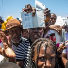 """Haitian citizens hold up their passports as they gather in front of the US Embassy in Tabarre, Haiti on July 10, 2021, asking for asylum after the assassination of President Jovenel Moise explaining that there is too much insecurity in the country and that they fear for their lives. - The widow of slain Haitian leader Jovenel Moise, who was critically wounded in the attack that claimed his life, issued her first public remarks since the assault, calling on the nation not to """"lose its way."""" According to Haitian authorities, an armed commando of 28 men -- 26 Colombians and two Haitian-Americans -- burst in and opened fire on the couple in their home. So far, 17 have been arrested, and at least three were killed. A handful remain at large, police say. No motive has been made public. (Photo by Valerie Baeriswyl / AFP)"""