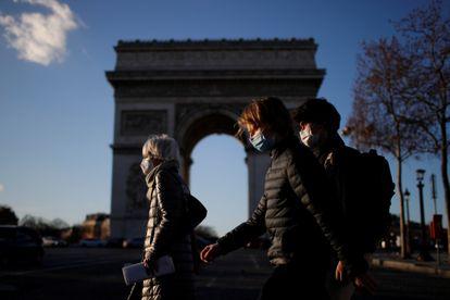 Pedestres caminham pela Champs Elysees, em Paris, com máscaras de proteção contra a covid-19, nesta segunda-feira, 25 de janeiro. Europa cobra transparência das farmacêuticas sobre vacinas.