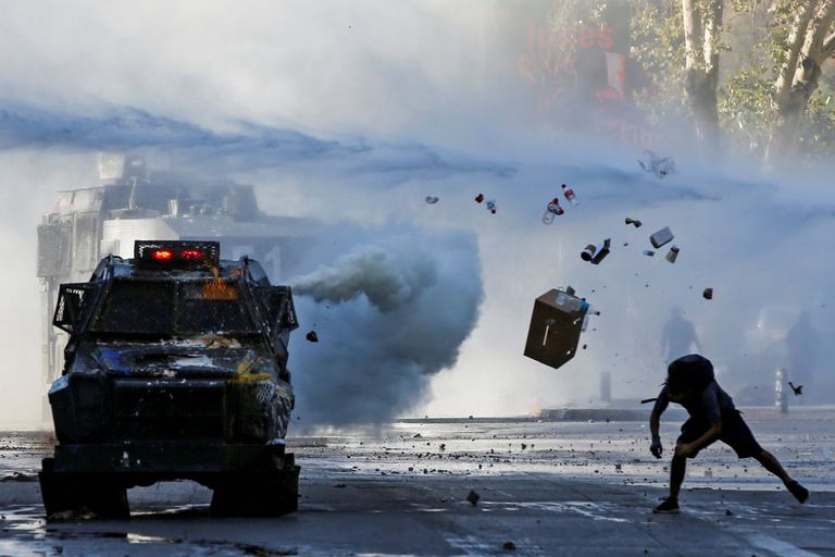 Um manifestante lança objetos em direção a um veículo blindado durante um protesto em Santiago do Chile.