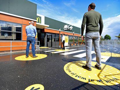 Clientes mantêm a distância social recomendada para entrar num McDonald's dos Países Baixos.