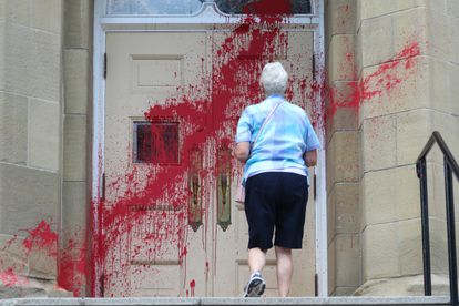 Uma fiel se aproxima da entrada da igreja presbiteriana Grace, atacada com tinta vermelha em Calgary, no dia 3.