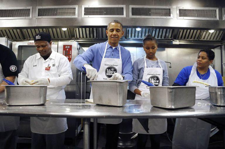Obama cozinha com sua filha e voluntários em um centro de caridade em Washington no dia de Martin Luther King.