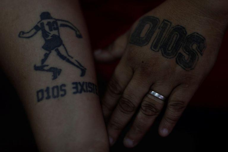 Mulher exibe tatuagens em homenagem a Diego Maradona em Buenos Aires.