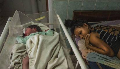 Rosa Sabina Briceno, de 22 anos, junto a seu bebê no ambulatório de Santo Domingo, após dar a luz em um táxi.