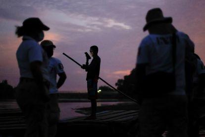 Agentes do Instituto Nacional de Migração vigiam o rio Suchiate, preparando-se para a chegada de uma caravana de migrantes.